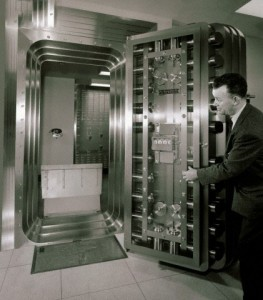 Side profile of a mature man opening a bank vault door